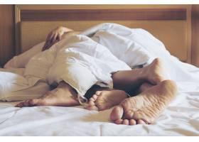 酒店房间白色床上的情侣专注于脚下_3805933