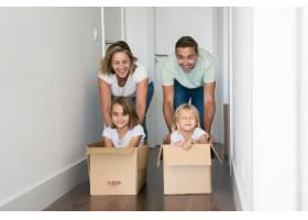 高加索父母推着纸箱里面装着孩子_10579228