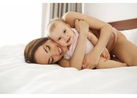 幸福美丽的母亲穿着睡衣躺在床上抱着她的_9028482