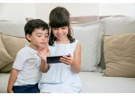开心兴奋的女孩和她的小弟弟坐在客厅的沙发_9988496