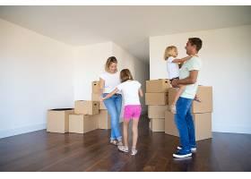 幸福的父母和两个女孩在搬进新公寓时在成堆_10608476