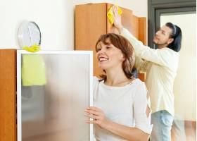 微笑的夫妇在家里打扫卫生_1473761