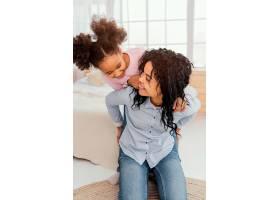 微笑的母亲和女儿在家中玩耍的前景_13108827