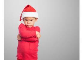 心烦意乱的小男孩戴着圣诞老人的帽子_941003