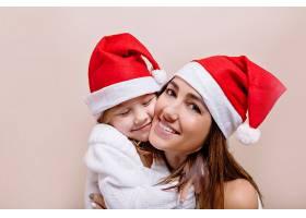 快乐微笑滑稽的母女俩戴着圣诞老人帽摆_12965120