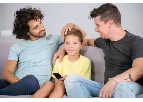 快乐的同性恋爸爸和儿子在家一起看电视节目_11298095