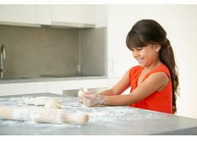 快乐的女孩在厨房桌子上用面粉揉面团凌乱_9649941