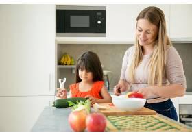 快乐的妈妈和女儿一起做饭女孩和她的母亲_9649837