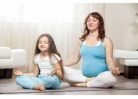 快乐的孕母和小女孩在家一起打坐_1280746