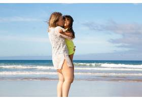 快乐的年轻妈妈和小女儿在海边度过休闲时光_11072653