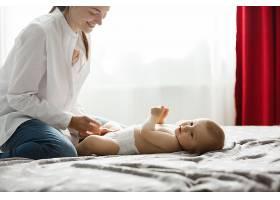 快乐的年轻妈妈在明亮的卧室里微笑着给她_9696788