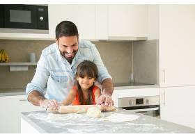 快乐的拉丁女孩和她的爸爸在厨房桌子上用面_9988364