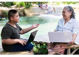孙子教他的老年女性使用笔记本电脑_5154265