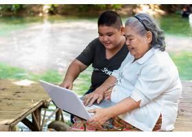 孙子教他的老年女性使用笔记本电脑_5154266