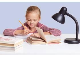 小可爱的小女孩坐在白色的书桌前做作业_8761275