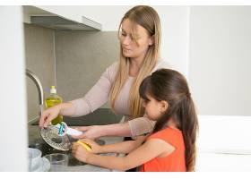 小女孩帮她妈妈洗盘子母女俩站在厨房水槽_9988569