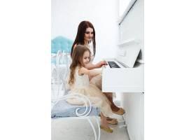 从后面看正在弹白色钢琴的母女俩_1120623
