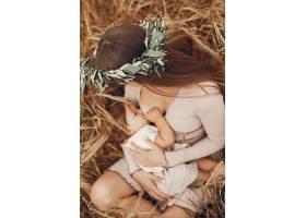 优雅的母亲带着可爱的小女儿在田野里_5557881