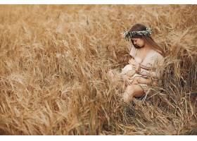 优雅的母亲带着可爱的小女儿在田野里_5557890