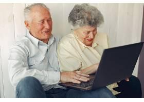 优雅的老两口坐在家里用笔记本电脑_6633778