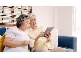 亚洲老年夫妇在家中的客厅里使用平板电脑和_4396332