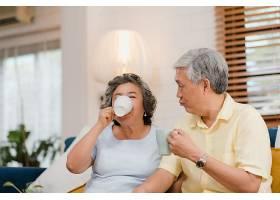 亚洲老年夫妇在家起居室里喝着热咖啡一起聊_4396369