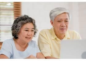 亚洲老年夫妇在起居室使用笔记本电脑与医生_4396397
