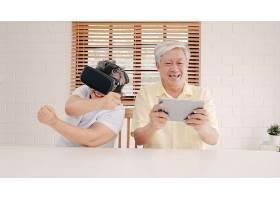 亚洲老年夫妇在起居室里使用平板电脑和虚拟_4396359