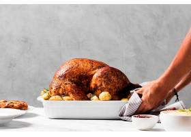 侧视手将火鸡放在桌子上_9894342