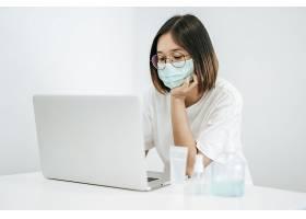一个女人戴着面具玩着笔记本电脑拿着一_8351652