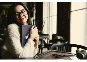一位女士温柔地拿着旧相册坐在咖啡馆里_1621073