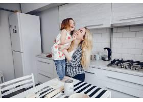 一位年轻漂亮的母亲带着她的小女儿在家里的_2533975