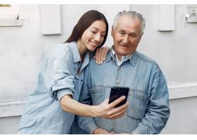 一位年轻的妇女在教她的祖父如何使用电话_7121838