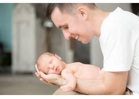一位微笑的年轻男子手心抱着一个新生儿_1280828