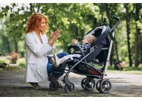 一位母亲带着她的小儿子坐在公园的一辆婴儿_5159122