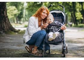 一位母亲带着她的小儿子坐在公园的一辆婴儿_5159123