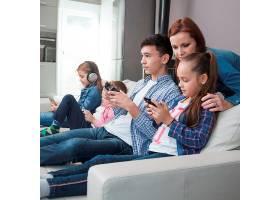 一名妇女看着正在玩电子游戏的青少年和女孩_2041365