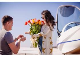 一名男子向一名站在飞机前的女子求婚_2438030