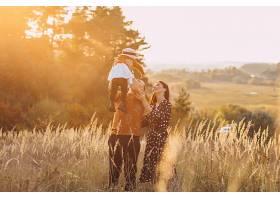 一家人带着他们的小女儿在秋天的田野里_5915979