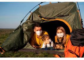 一家人戴着口罩坐在帐篷里看着他们的狗_10827232
