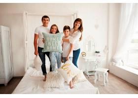 一家人站在床上枕头上放着甜蜜的家书_5116560