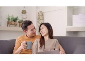 一对亚洲夫妇在家中的起居室里使用笔记本电_4014655