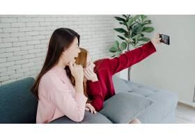 一对亚洲女同性恋夫妇在家中的客厅里使用智_4015335