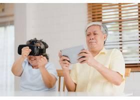 一对亚洲老年夫妇在客厅里使用平板电脑和虚_4396400