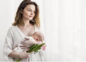 美丽的母亲抱着她的孩子站在白色窗帘旁看着_4056889