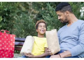 美国黑人小女孩和父亲在公园里吃爆米花_11139198