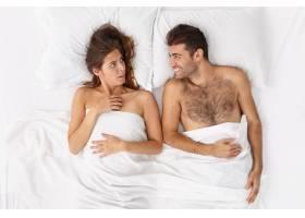 近距离观察躺在床上的一对夫妇他们盖着白_12950733