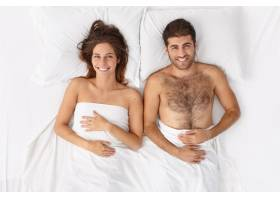 近距离观察躺在床上的一对夫妇他们盖着白_12950751