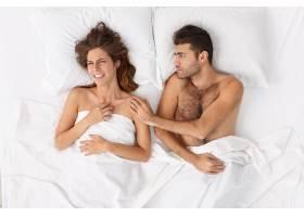 近距离观察躺在床上的一对夫妇他们盖着白_12951060