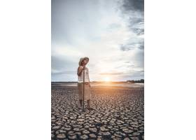 那个女人站在他的手上在干燥的土壤上抓了_5469317